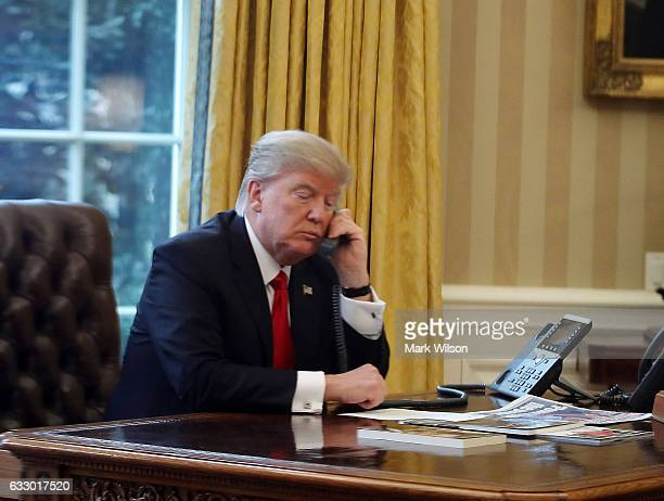 President Donald Trump is seen through a window speaking on the phone with King of Saudi Arabia Salman bin Abd alAziz Al Saud in the Oval Office of...
