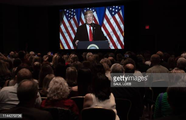 President Donald Trump is watched on a large screen as he speaks during the National Association of Realtors Legislative Meetings and Trade Expo in...