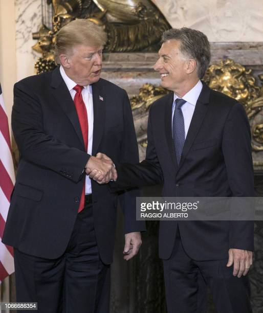 US President Donald Trump is welcomed by Argentina's President Mauricio Macri at Casa Rosada presidential house in Buenos Aires on November 30 to...