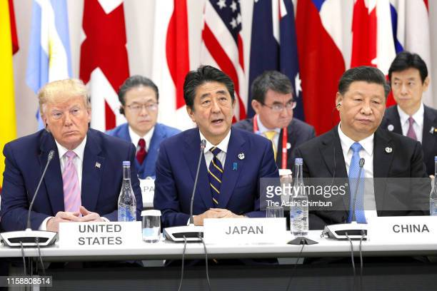 US President Donald Trump Japanese Prime Minister Shinzo Abe and Chinese President Xi Jinping attend a conference on the Digital Economy on the first...