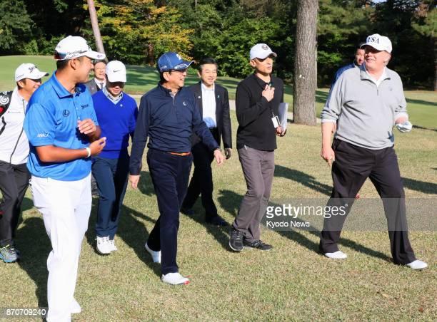 US President Donald Trump Japanese Prime Minister Shinzo Abe and professional golfer Hideki Matsuyama walk at Kasumigaseki Country Club in Kawagoe...