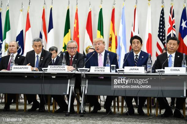 TOPSHOT US President Donald Trump Japan's Prime Minister Shinzo Abe and China's President Xi Jinping attend a meeting at the G20 Summit in Osaka on...