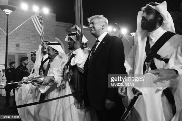 US President Donald Trump joins dancers with swords at a welcome ceremony ahead of a banquet at Murabba Palace in Riyadh on May 20 2017 / AFP PHOTO /...