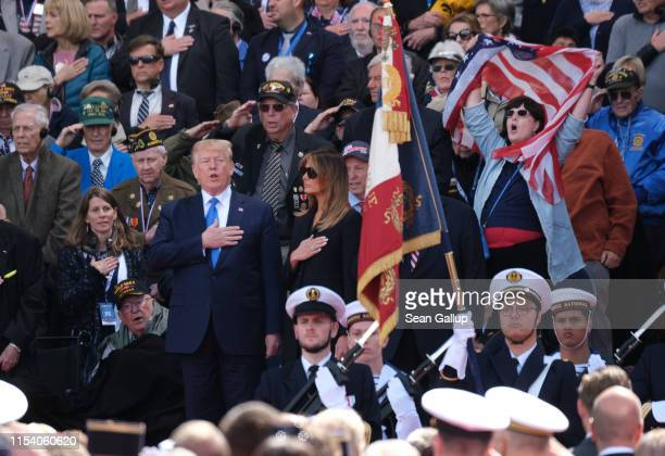 S President Donald Trump joins in in singing the American national anthem as First Lady Melania Trump looks on at the main ceremony to mark the 75th...