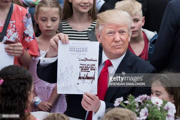 President Donald Trump joins others to write notes to service members during the Easter Egg Roll on the South Lawn of the White House April 17 2017...