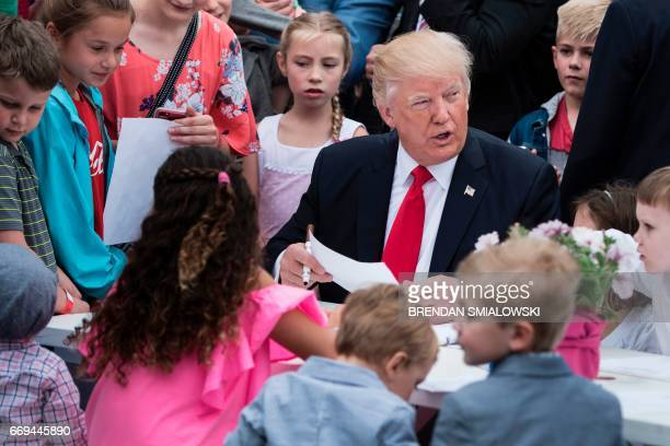 US President Donald Trump joins others to write notes to service members during the Easter Egg Roll on the South Lawn of the White House April 17...