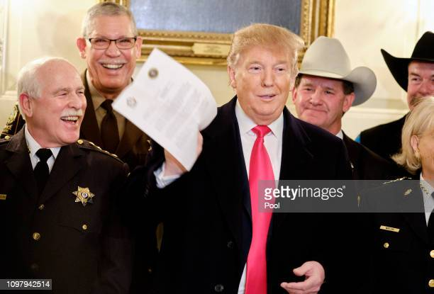 US President Donald Trump jokes about a letter given to him by a sheriff after meeting with sheriffs from across the country in the Diplomatic...