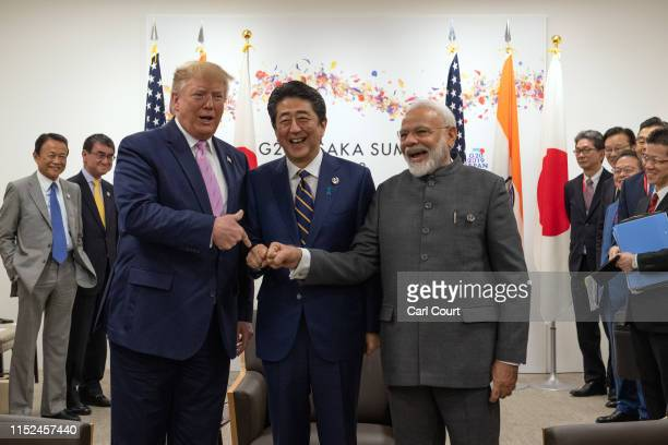 President Donald Trump jokes to the media about fist bumping with Japan's Prime Minister Shinzo Abe and India's Prime Minister Narendra Modi during a...