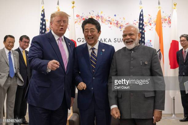 President Donald Trump jokes to the media about fist bumping with Japan's Prime Minister, Shinzo Abe, and India's Prime Minister, Narendra Modi,...