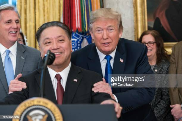 US President Donald Trump jokes with Broadcom CEO Hock Tan as he announces that Broadcom woud be moving back to the US in the Oval Office at the...