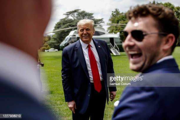 President Donald Trump jokes with supporters as he departs the White House for a trip to Ohio where he will visit a Whirlpool factory on August 6,...