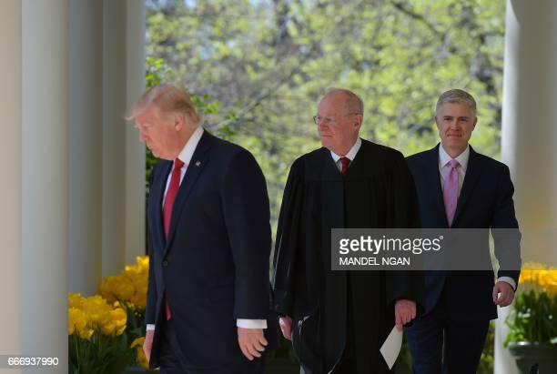 US President Donald Trump Justice Anthony Kennedy and Neil Gorsuch make their way to the Rose Garden for Gorsuch's swearingin ceremony as an...