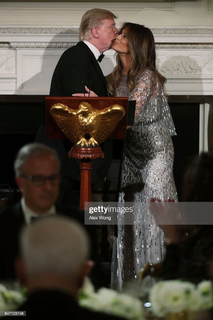 U.S. President Donald Trump kisses first lady Melania Trump during a reception at the State Dining Room of the White House September 14, 2017 in Washington, DC. President Trump and the first lady hosted a reception for the White House Historical Association.