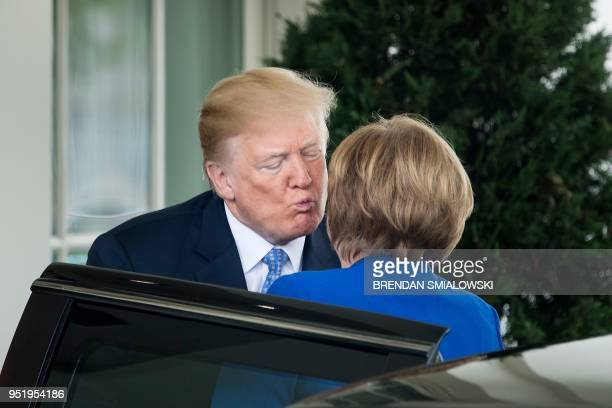 US President Donald Trump kisses German Chancellor Angela Merkel as he welcomes her to the White House on April 27 2018 in WashingtonDC