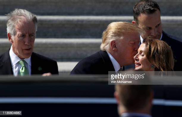 S President Donald Trump kisses Speaker of the House Nancy Pelosi while departing the US Capitol following a St Patrick's Day celebration on March 14...