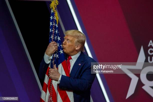 President Donald Trump kisses the flag of the United States of America at the annual Conservative Political Action Conference at Gaylord National...