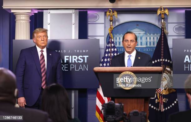 President Donald Trump (L0 looks on as United States Secretary of Health and Human Services Alex Azar speaks to the press in the James Brady Press...