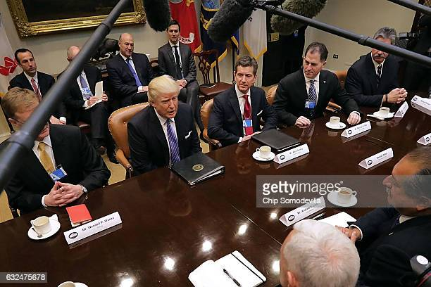 S President Donald Trump leads a meeting with invited business leaders and members of his staff in the Roosevelt Room at the White House January 23...