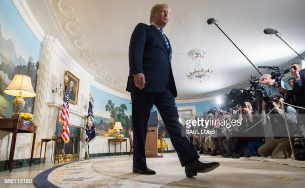 US President Donald Trump leaves after announcing his decision about the nuclear deal with Iran during a speech from the Diplomatic Reception Room at...