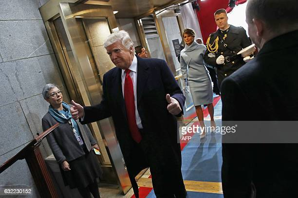 US President Donald Trump leaves after being sworn in followed by first lady Melania Trump on the West Front of the US Capitol during his...