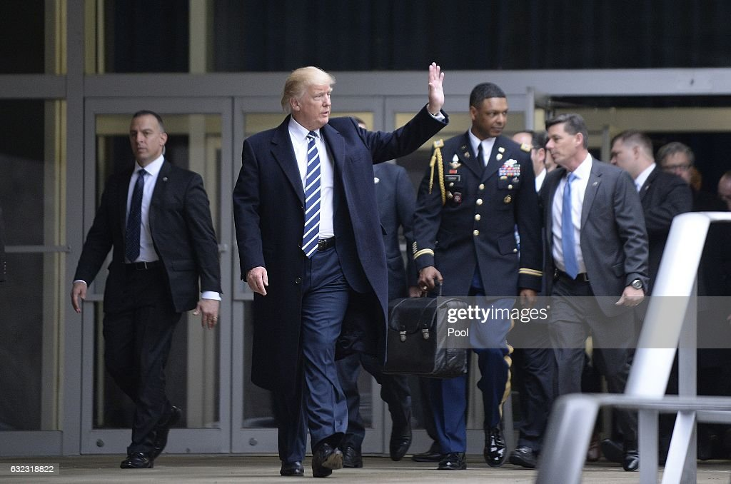 US President Donald Trump leaves the CIA headquarters after speaking to 300 people on January 21, 2017 in Langley, Virginia . Trump spoke with about 300 people in his first official visit with a government agency. In the background a military aid carries the 'football', with launch codes for nuclear weapons.