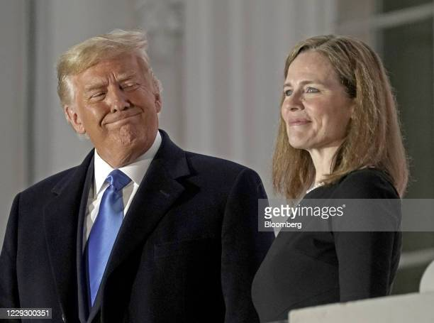 President Donald Trump, left, and Amy Coney Barrett, associate justice of the U.S. Supreme Court, stand on a balcony during a ceremony on the South...