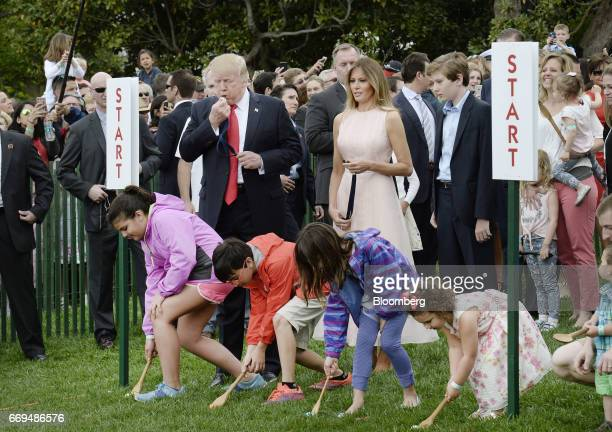 US President Donald Trump left and First Lady Melania center blow a whistle to start the annual Easter Egg Roll on the South Lawn of the White House...