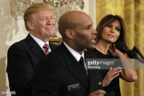 US President Donald Trump left and First Lady Melania Trump right smile as Vice Admiral Jerome Adams the US Surgeon General speaks during a National...