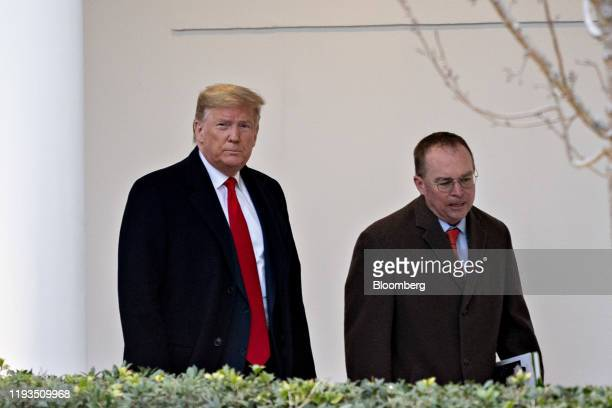 US President Donald Trump left and Mick Mulvaney acting White House chief of staff walk through the Colonnade of the White House before boarding...