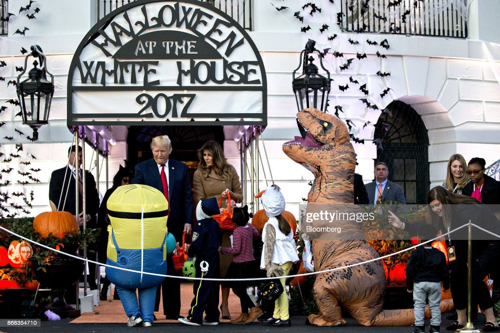 U.S. President Donald Trump, left, and U.S. First Lady Melania Trump, center, greet children dressed up in costumes during a Halloween event on the South Lawn of the White House in Washington, D.C., U.S., on Monday, Oct. 30, 2017. Trump greeted costumed children during a traditional Halloween trick-or-treat at the White House, on the same day as Special Counsel Robert Mueller's investigation took a major turn as authorities charged three people -- a former campaign chief, his business associate and an ex-policy adviser -- with crimes including money laundering, lying to the FBI and conspiracy. Photographer: Andrew Harrer/Bloomberg via Getty Images