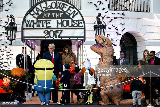 US President Donald Trump left and US First Lady Melania Trump center greet children dressed up in costumes during a Halloween event on the South...