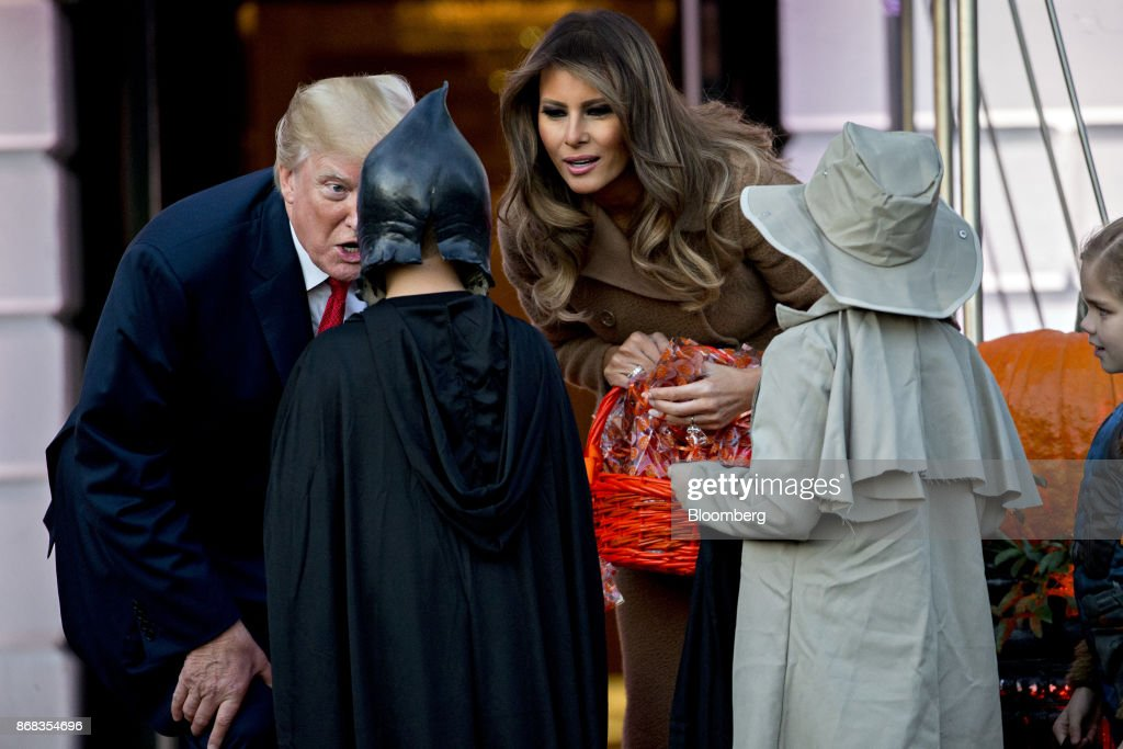 U.S. President Donald Trump, left, and U.S. First Lady Melania Trump greet children dressed up in costumes during a Halloween event on the South Lawn of the White House in Washington, D.C., U.S., on Monday, Oct. 30, 2017. Trump greeted costumed children during a traditional Halloween trick-or-treat at the White House, on the same day as Special Counsel Robert Mueller's investigation took a major turn as authorities charged three people -- a former campaign chief, his business associate and an ex-policy adviser -- with crimes including money laundering, lying to the FBI and conspiracy. Photographer: Andrew Harrer/Bloomberg via Getty Images