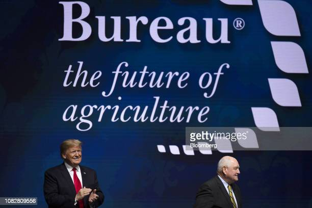US President Donald Trump left applauds as Sonny Perdue US secretary of agriculture exits the stage during the 100th American Farm Bureau Federation...