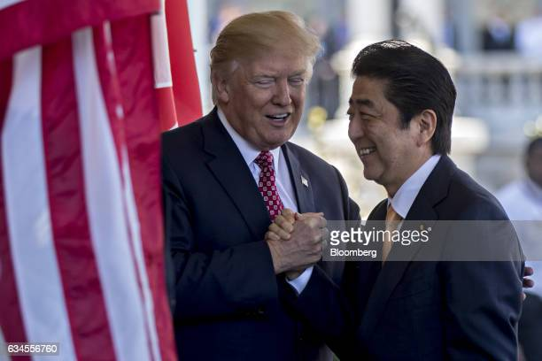 US President Donald Trump left greets Shinzo Abe Japans prime minister as he arrives to the West Wing of the White House in Washington DC US on...
