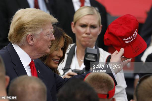 US President Donald Trump left holds an autographed 'Make America Great Again' hat as he greets guests with First Lady Melania Trump second left at a...