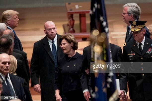 President Donald Trump, left, looks at former Florida Gov. Jeb Bush, right, as Bush family members follow the flag-draped casket of former President...