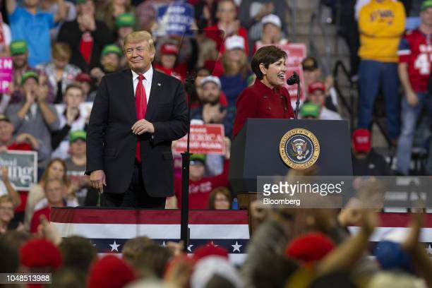 US President Donald Trump left looks on as Kim Reynolds governor of Iowa speaks at a rally in Council Bluffs Iowa US on Tuesday Oct 9 2018 Trump said...