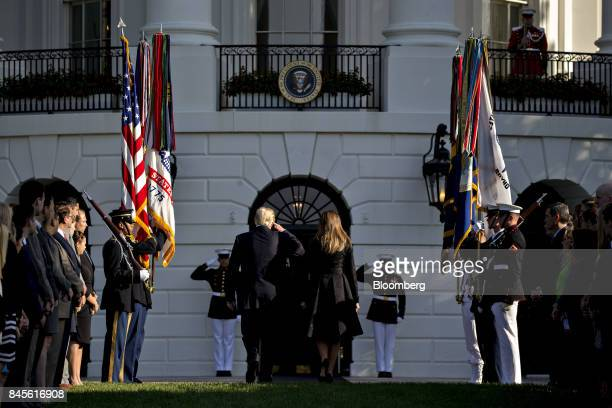 US President Donald Trump left salutes next to US First Lady Melania Trump while walking into the White House after leading a moment of silence with...