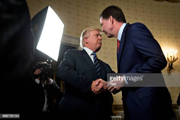 S President Donald Trump left shakes hands with James Comey director of the Federal Bureau of Investigation during an Inaugural Law Enforcement...
