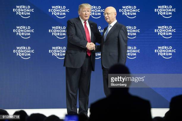 US President Donald Trump left shakes hands with Klaus Schwab chairman of the World Economic Forum during a special address on the closing day of the...