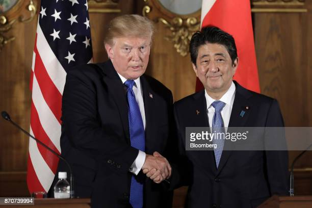 US President Donald Trump left shakes hands with Shinzo Abe Japan's prime minister during a news conference at Akasaka Palace in Tokyo Japan on...