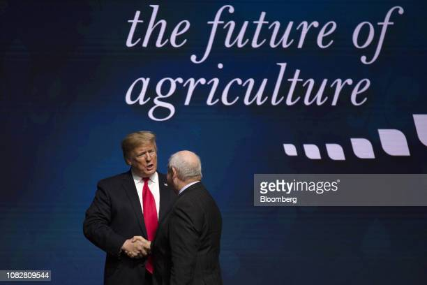 US President Donald Trump left shakes hands with Sonny Perdue US secretary of agriculture on stage during the 100th American Farm Bureau Federation...
