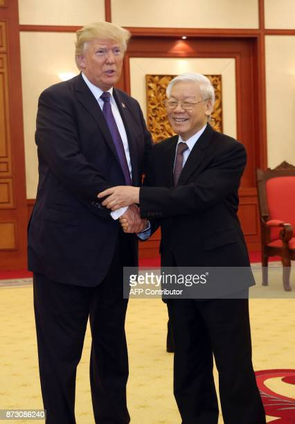President Donald Trump left shakes hands with Vietnam Communist Party General Secretary Nguyen Phu Trong at meeting in Hanoi on November 12 2017...