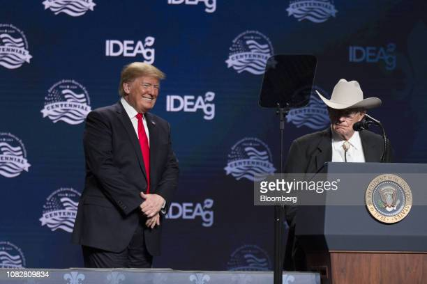 US President Donald Trump left smiles as rancher James Chilton speaks during the 100th American Farm Bureau Federation Convention in New Orleans...