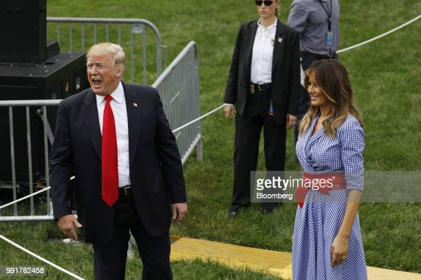 US President Donald Trump left speaks as First Lady Melania Trump right looks on while greeting guests at a picnic for military families in...