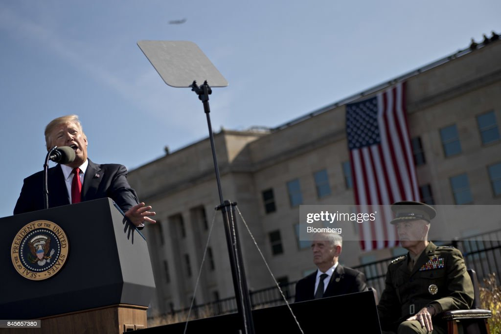 U.S. President Donald Trump, left, speaks as General Joseph Dunford, chairman of the Joint Chiefs of Staff, right and Jim Mattis, U.S. secretary of defense, listen, during a ceremony to commemorate the September 11, 2001 terrorist attacks, at the Pentagon in Washington, D.C., U.S., on Monday, Sept. 11, 2017. Trump is presiding over his first 9/11 commemoration on the 16th anniversary of the terrorist attacks that killed nearly 3,000 people when hijackers flew commercial airplanes into New York's World Trade Center, the Pentagon and a field near Shanksville, Pennsylvania. Photographer: Andrew Harrer/Bloomberg via Getty Images