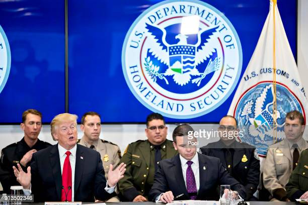 US President Donald Trump left speaks as Kevin McAleenan acting commissioner of the US Customs and Border Protection center listens while...