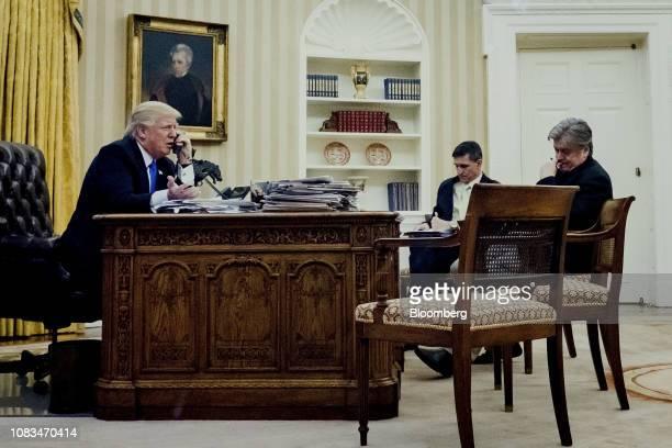 S President Donald Trump left speaks on the phone with Malcolm Turnbull Australia's prime minister as retired Lieutenant General Michael Flynn US...