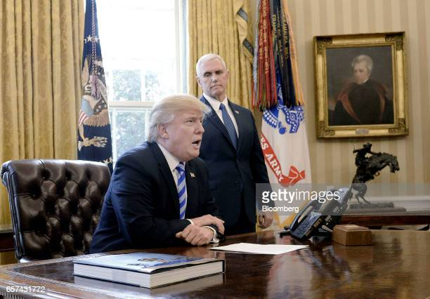 US President Donald Trump left speaks to members of the media as US Vice President Mike Pence stands at the Oval Office in Washington DC US on Friday...