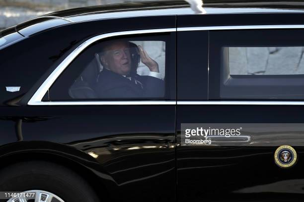 US President Donald Trump left waves next to First Lady Melania Trump inside his motorcade as they leave Haneda Airport in Tokyo Japan on Saturday...